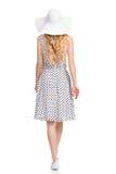 Vue arrière de femme de marche dans la robe, le chapeau de Sun et des espadrilles pointillés par blanc Photos stock