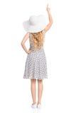 Vue arrière de femme de pointage dans la robe d'été et le chapeau de Sun Images stock
