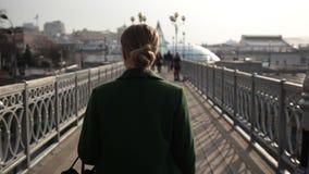 Vue arrière de femme marchant loin sur le pont banque de vidéos