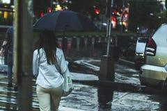 Vue arrière de femme marchant pendant la pluie dans la ville image libre de droits