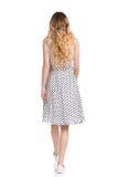Vue arrière de femme de marche dans la robe et des espadrilles pointillées par blanc Photographie stock libre de droits