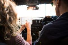 Vue arrière de femme montrant la tablette à l'homme Photographie stock libre de droits