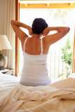 Vue arrière de femme se réveillant dans le lit dans le matin Photographie stock libre de droits
