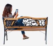 Vue arrière de femme se reposant sur le banc et les regards à l'écran le comprimé images libres de droits