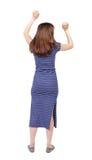 Vue arrière de femme A soulevé son poing dans le signe de victoire Photographie stock libre de droits