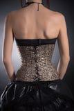 Vue arrière de femme utilisant le corset d'or Photographie stock