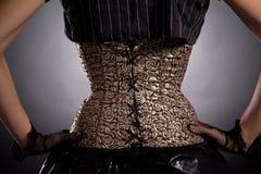Vue arrière de femme utilisant le corset d'or Photographie stock libre de droits