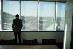 Vue arrière de fenêtre se tenante prêt d'homme d'affaires dans le lieu de réunion photo stock