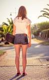 Vue arrière de fille avec une planche à roulettes dehors l'été Images stock