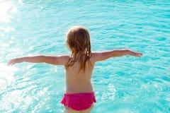 Vue arrière de fille d'enfants dans la plage au coucher du soleil image stock