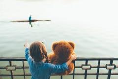 Vue arrière de fille embrassant un ours de nounours mignon montrant à un canoë Image libre de droits