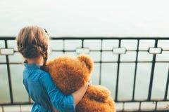 Vue arrière de fille embrassant un ours de nounours mignon regardant au lac Images stock
