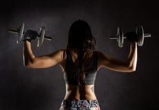 Vue arrière de fille sexy sportive avec des haltères sur un fond foncé Athlète faisant des exercices dans le gymnase Photographie stock