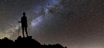 Vue arrière de fille de touristes de jeune randonneur mince sur le dessus de montagne rocheuse sur le ciel étoilé de nuit foncée  images stock