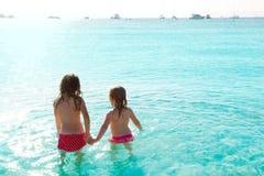 Vue arrière de filles d'enfants dans la plage au coucher du soleil Images stock