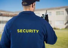 Vue arrière de garde de sécurité utilisant la radio contre la maison image stock