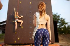 Vue arrière de jeune femme active de gingembre dans des guêtres se tenant avec la corde sur l'épaule contre s'élever artificiel d photographie stock libre de droits