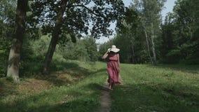 Vue arrière de jeune femme avec le chapeau fonctionnant sur le pré, mouvement lent banque de vidéos