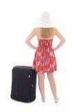 Vue arrière de jeune femme de blondie dans la robe rouge avec l'isolant de valise Photographie stock