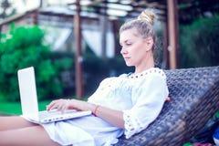 Vue arrière de jeune femme effectuant le travail à distance au whil moderne d'ordinateur portable images stock
