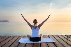 Vue arrière de jeune femme faisant le yoga photos stock