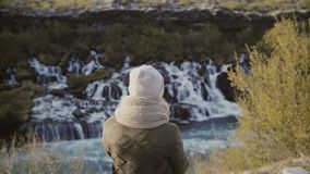 Vue arrière de jeune femme se tenant en vallée de montagne et regardant sur des cascades en Islande, explorant la nature banque de vidéos