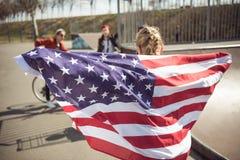 Vue arrière de jeune fille se tenant avec le drapeau américain et regardant des amis Photographie stock