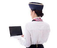 Vue arrière de jeune hôtesse montrant l'ordinateur portable avec l'écran vide i Photographie stock libre de droits