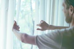 Vue arrière de jeune homme dans occasionnel au rooma confortable à la maison regardant la fenêtre de throung pendant le matin images libres de droits