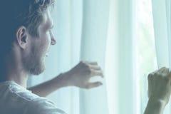 Vue arrière de jeune homme dans occasionnel au rooma confortable à la maison regardant la fenêtre de throung pendant le matin image libre de droits