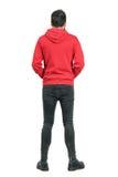 Vue arrière de jeune homme en jeans serrés et bottes utilisant le hoodie rouge Images stock