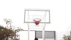 Vue arrière de jeune homme jouant le basket-ball et jetant une boule au panier avec succès Tir au ralenti banque de vidéos