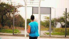 Vue arrière de jeune homme jouant le basket-ball : il saute et jette une boule au panier avec succès Au ralenti banque de vidéos
