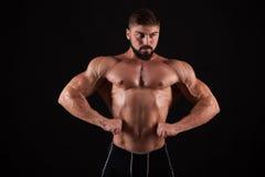 Vue arrière de jeune homme musculaire en bonne santé avec ses bras étirés d'isolement sur le fond noir photos libres de droits