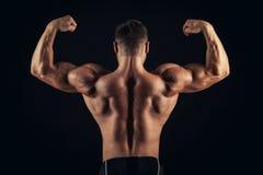 Vue arrière de jeune homme musculaire en bonne santé avec ses bras étirés d'isolement sur le fond noir Photographie stock