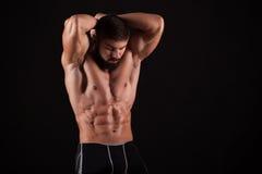Vue arrière de jeune homme musculaire en bonne santé avec ses bras étirés d'isolement sur le fond noir Photo libre de droits