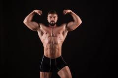 Vue arrière de jeune homme musculaire en bonne santé avec ses bras étirés d'isolement sur le fond noir Photo stock