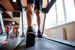 Vue arrière de jeune sportif fonctionnant sur le tapis roulant dans le gymnase Images stock