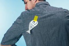 vue arrière de l'homme avec des poissons sur de bande le dos collant dessus, jour d'imbéciles d'avril images stock
