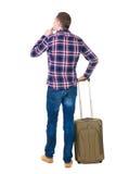 Vue arrière de l'homme avec la valise verte recherchant Images stock