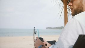 Vue arrière de l'homme d'affaires réussi avec la boisson de fruit et de l'ordinateur portable vérifiant la montre intelligente da banque de vidéos