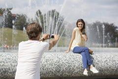 Vue arrière de l'homme enregistrant la femme en vidéo contre la fontaine Photos stock