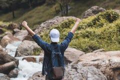 Vue arrière de l'homme gai de voyageur d'Asain soulevant le fond scénique de montagne de mains dehors Relaxation de voyage et réu photographie stock libre de droits