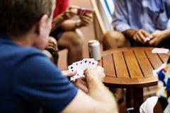 Vue arrière de l'homme jouant le jeu de carte avec des amis Images stock