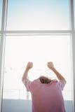 Vue arrière de l'homme se penchant contre le verre de fenêtre Photographie stock