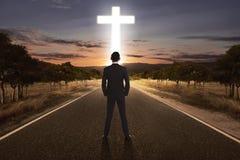 Vue arrière de l'homme se tenant sur la rue avec la croix lumineuse Images libres de droits
