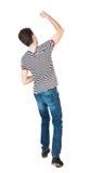 Vue arrière de l'homme A soulevé son poing dans le signe de victoire Photos libres de droits