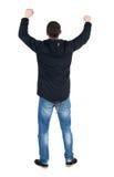 Vue arrière de l'homme A soulevé son poing dans le signe de victoire Image libre de droits