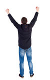 Vue arrière de l'homme A soulevé son poing dans le signe de victoire Images stock