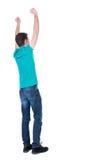Vue arrière de l'homme A soulevé son poing dans le signe de victoire Images libres de droits